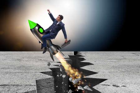 Businessman flying on rocket from rock gap Imagens - 83544320
