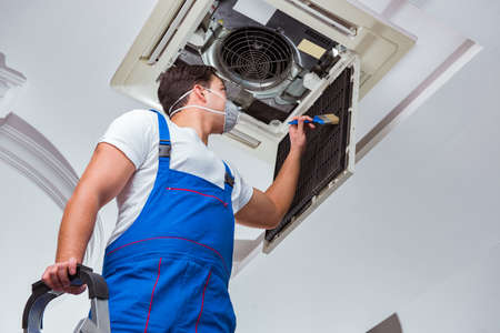 Worker repairing ceiling air conditioning unit Stockfoto