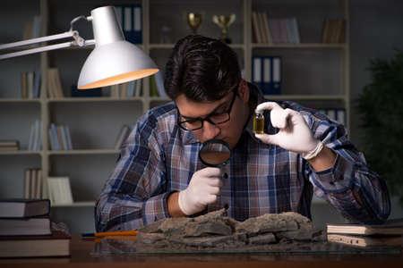 事務所で夜遅くまでの作業の考古学者 写真素材