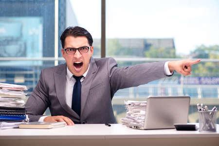 Boze zakenman met te veel werk in het kantoor