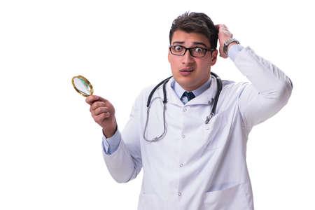 Jonge mannelijke arts met een uitziend vergrootglas dat op witte achtergrond wordt geïsoleerd