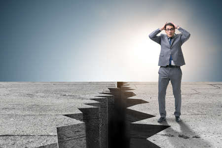 Businessman standing scared next to cliff Stock Photo