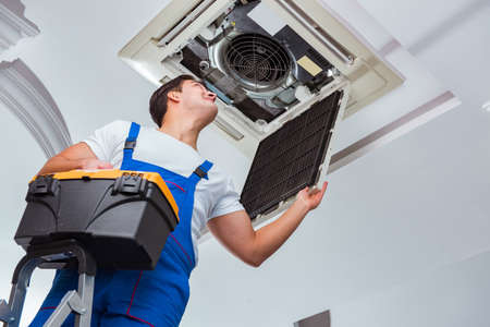 Worker repairing ceiling air conditioning unit Archivio Fotografico