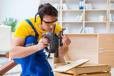 Repairman carpenter cutting sawing a wooden board with an electr Banco de Imagens