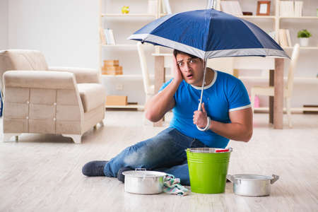 Man at home dealing with neighbor flood leak Stockfoto