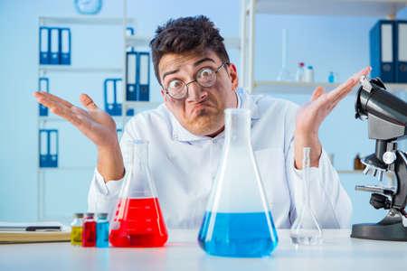 Grappige gekke chemicus die in een laboratorium werkt Stockfoto