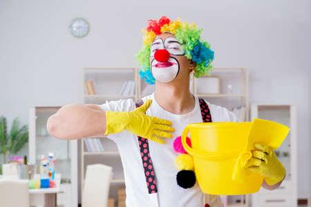 Grappige clown die thuis het schoonmaken doet Stockfoto