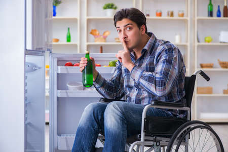 Young disabled injured man opening the fridge door Stock Photo