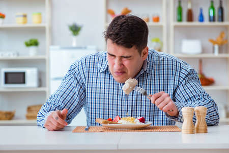 Man eating tasteless food at home for lunch