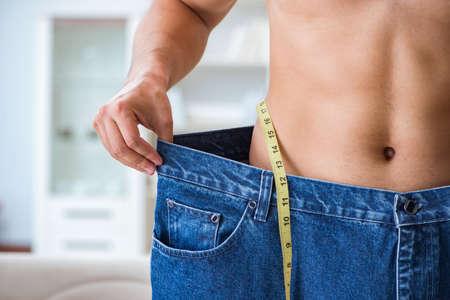 대형 체중 감량 개념의 바지를 입은 남자 스톡 콘텐츠