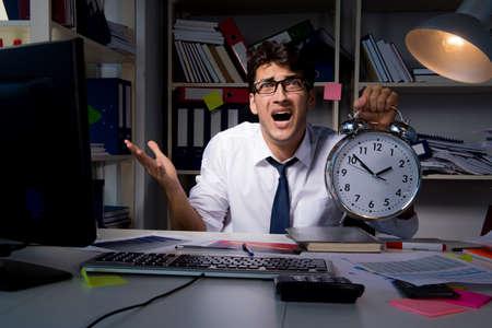 Mensenzakenman die late uren in het bureau werken