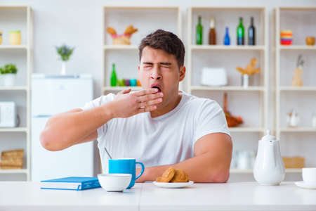 Man falling asleep during his breakfast after overtime work Stock Photo