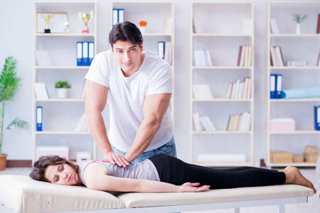 Young doctor chiropractor massaging female patient woman