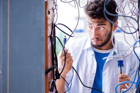 Electrician trying to untangle wires in repair concept Stok Fotoğraf