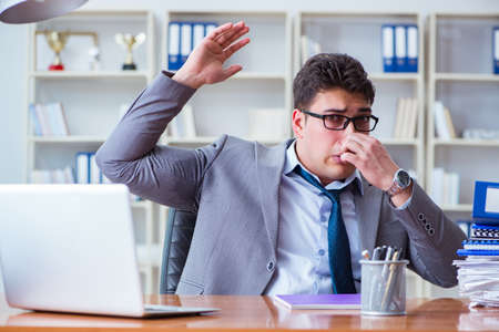 Businessman sweating excessively smelling bad in office at workp 스톡 콘텐츠