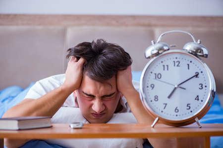 Man in bed gefrustreerd lijden aan slapeloosheid met een alarm cloc