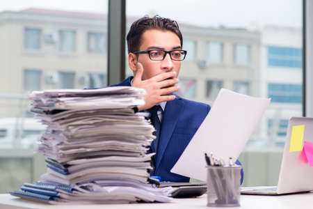 Workaholic businessman overworked with too much work in office 版權商用圖片