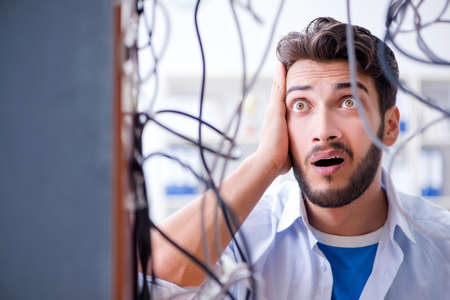 Electrician trying to untangle wires in repair concept Banco de Imagens