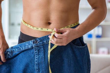 Mann in übergroßen Hosen im Gewichtsverlustkonzept