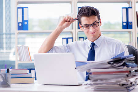 Businessman with excessive work paperwork working in office Stock Photo