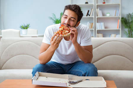 L'uomo che mangia pizza avendo un takeaway a casa rilassante riposo