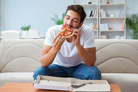 Man die pizza eet met een afhaalmaaltijd thuis ontspannend rust
