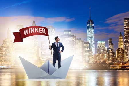 勝つコンセプトで紙ボート船に乗っているビジネスマン 写真素材