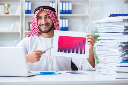 オフィスで働くアラブのビジネスマンは、パイで書類を行う 写真素材