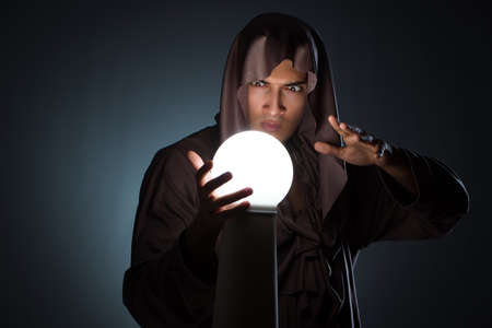 Young wizard with crystal ball in dark room Stock fotó - 89516446