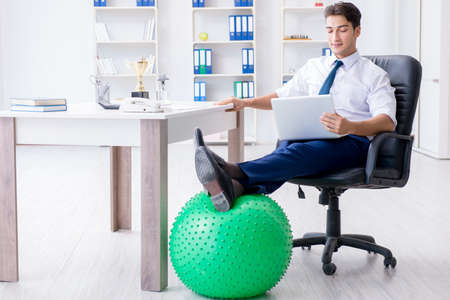 Young businessman doing sports stretching at workplace Фото со стока
