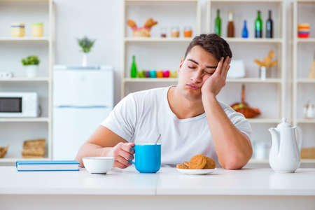 Man falling asleep during his breakfast after overtime work Standard-Bild
