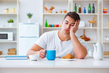Man Einschlafen während seines Frühstücks nach Überstunden Standard-Bild