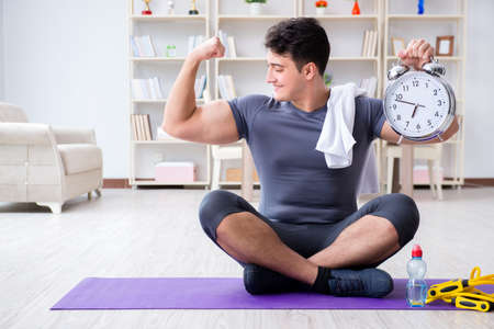 Young man exercising at home in sports and healthy lifestyle con