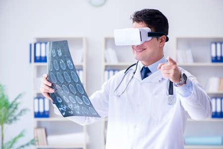 Jovem médico que examina a ressonância magnética através de óculos VR Foto de archivo