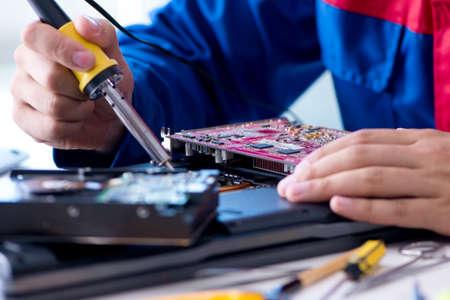テクニカルサポートで働く修理工は、コンピュータのラップトップtrを固定します