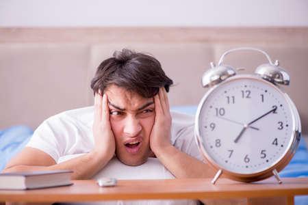 Man in bed gefrustreerd lijden aan slapeloosheid met een wekker