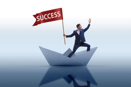 Businessman riding paper boat ship in success concept