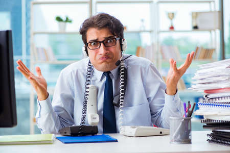 Unhappy angry call center worker frustrated with workload Foto de archivo