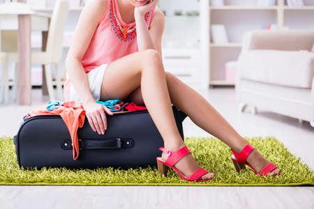 Vrouw die probeert om alle kleding aan suitacase vóór vakantie te passen Stockfoto