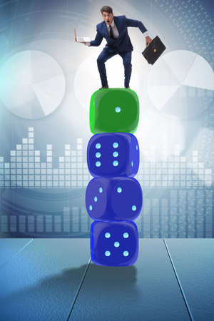 Businessman balancing on top of dice stack in uncertainty concep Banque d'images