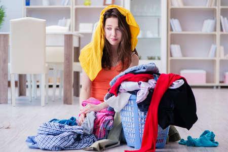 Beklemtoonde vrouw die wasserij thuis doet Stockfoto