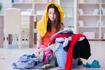 Stressed woman doing laundry at home Stock fotó - 90161383