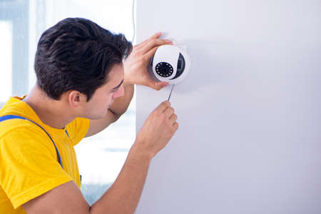 Contractor installing surveillance CCTV cameras in office