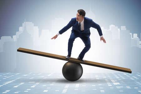 Hombre de negocios tratando de equilibrar en bola y balancín