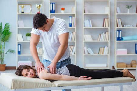 Jonge artsenchiropractor die vrouwelijke geduldige vrouw masseren Stockfoto