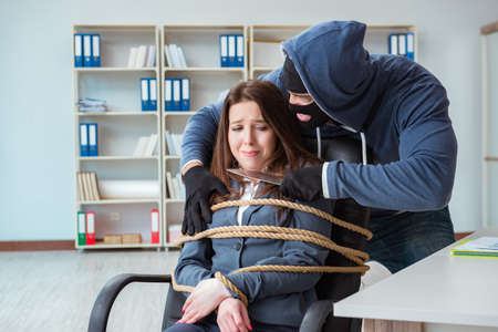 Criminal taking businesswoman as hostage in office Archivio Fotografico