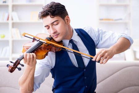 自宅でバイオリンを練習している若いミュージシャンの男性 写真素材