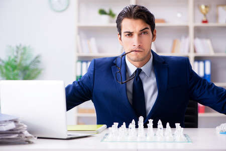 Young businessman playing glass chess in office Foto de archivo