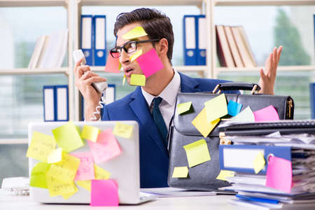 Businessman with reminder notes in multitasking concept Imagens