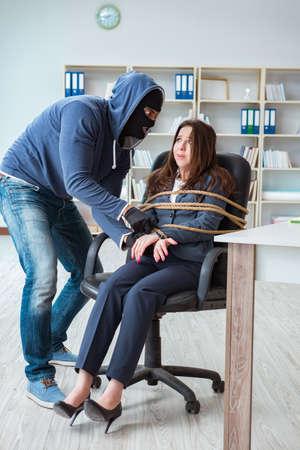 Criminal taking businesswoman as hostage in office Stockfoto
